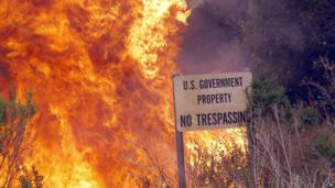 A brush fire burns a sign at a shooting range on the beach at Naval Base Ventura County 3 May 2013