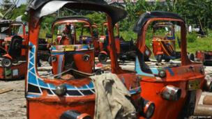 A worker cuts up Indonesian rickshaws