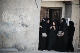 Bahraini women take shelter outside the entrance of a house