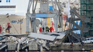 Rescuers stand on the rubble of a former harbour control tower, all that remains standing of which is a tilted metal staircase.
