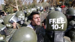 A student protester is detained during a riot at a rally demanding Chiles government reform the education system in Santiago, 8 May 2013.