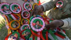 A vendor arranges badges of Pakistani politician and former cricketer Imran Khan