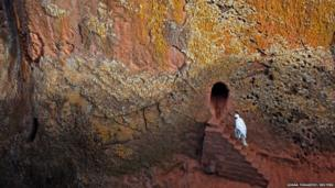An Orthodox Christian walks into one of 11 monolithic rock-cut churches in Lalibela
