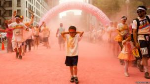 Runners pass through pink clouds during the Color Run 5km in Seattle, Washington