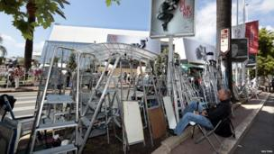 Man sits next to stepladders in Cannes, France (14 May 2013)