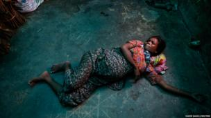 Roma Hattu, a Rohingya Muslim woman who is nine months pregnant, grimaces while experiencing labour pains on the bare floor of a former rubber factory