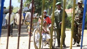 Men from the M23 rebel group and a tricycle rider in Bunagana town in eastern Democratic Republic of Congo on 14 May 2013