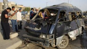 Residents gather at the site of a car bomb attack in Baghdad's Sadr City (16 May 2013)