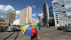 A woman with an umbrella bearing the image of US President Barack Obama prepares to cross the road in Zimbabwe's capital Harare on 10 May 2013