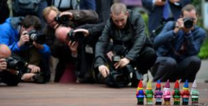 Photographers gather around garden gnomes during the Chelsea Flower Show press day in London