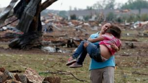 A woman carries a child through a field near the collapsed Plaza Towers Elementary School in Moore
