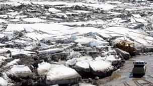 A bulldozer pushes Yukon River ice out of the way