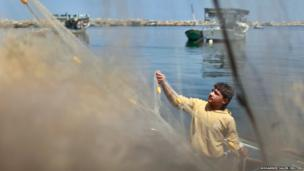 A Palestinian fisherman prepares his net at the seaport of Gaza City.