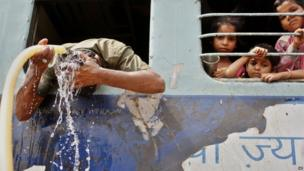 An Indian commuter pours water over his head to cool off as young children watch from a window at a railway station in Allahabad