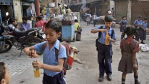 Indian schoolchildren make cold drinks as they walk to school in Delhi