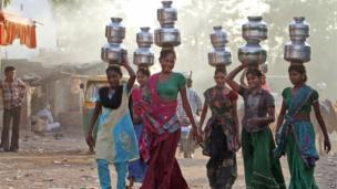 Indian village girls carry water in pitchers on their heads at Juval village, about 40km from Ahmedabad