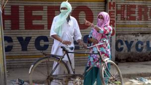 An Indian couple cover their face as they stand near bicycle on the roadside in Amritsar