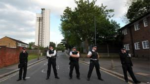 Five police officers block access to a road in Woolwich