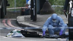 An police forensic investigator in a blue overall and white mask examines the ground