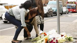 Two women lay flowers in Woolwich