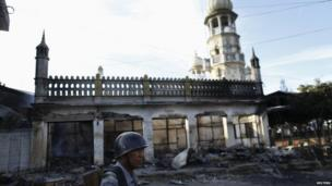 A soldier stands in front of a mosque damaged in the violence in Lashio, Burma