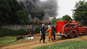 Firemen stand with a fire engine outside burning houses destroyed during fighting between Muslims and Buddhists in Lashio