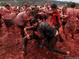 Revellers play with tomato pulp during the annual Tomatina