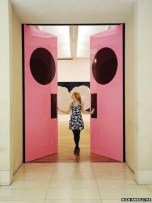 Tate Britain employee Ellie Blanchette walks through How to paint a door 2013 by artist Gary Hume during a press view at Tate Britain, London