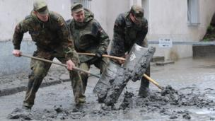 Soldiers shovel mud from the streets of Passau, Germany, on 4 June 2013