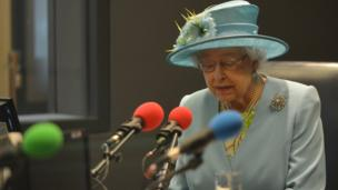 The Queen speaking into a microphone
