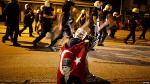 A protester with a Guy Fawkes' mask sits as riot police pass in central Ankara on 11 June 2013
