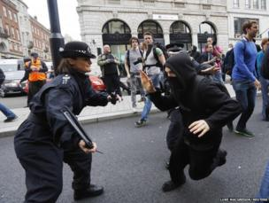 A protester demonstrating against the upcoming G8 summit tries to evade a police officer in central London