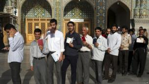 Iranian men display identification cards as they line up to vote in Qom. 14 June 2013.