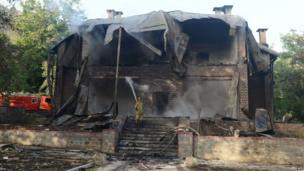 A Pakistani firefighter extinguishes a fire which gutted a historical building in Ziarat, south-east of Quetta, 15 June