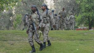 Pakistani troops at the scene of a blaze which gutted a historical building in Ziarat, south-east of Quetta, on 15 June