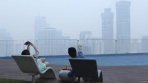 A couple take a picture of the smog-filled skyline in Singapore on 19 June 2013