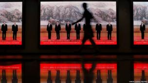 A pedestrian walks past electronic signs displaying pictures of China's Politburo