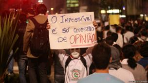 A masked protester holds up a placard during protests in Brazil, 17 June 2013
