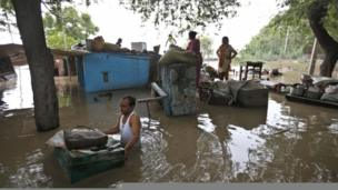 A man drags a trunk to higher ground after floodwaters inundated homes along the banks of the Yamuna River, in New Delhi, India, Wednesday, June 19, 2013