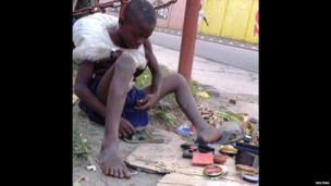 A child repairing a shoe on the side of the road in Kinshasa, DR Congo - Sunday 16 June 2013