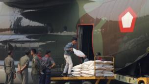 Workers load sacks of salt that will be used for cloud seeding to induce rain in Pekanbaru, Riau province, June 22