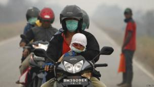 People wear surgical masks as they ride motorcycles in Dumai, Indonesia's Riau province, June 22