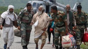 Indian defence personnel assist rescued civilians from the Gangotri area after being flown to safety on board an Indian Air Force Mi-17 transport helicopter at Dharasu in Uttarakhand