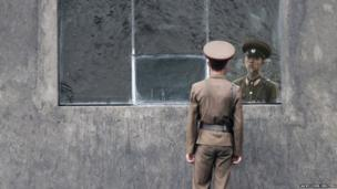 A North Korean soldier stands in front of a window along the banks of Yalu River near the North Korean town of Sinuiju