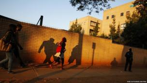 The sun rises as people walk past Pretoria hospital where Nelson Mandela is staying