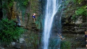 Boys in Georgia jumping off a rock face as water cascades down its surface