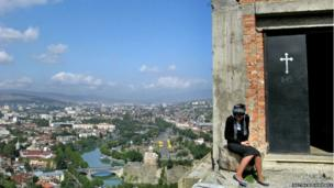 A woman seated outside a church door on heights over looking Tbilisi, Georgia