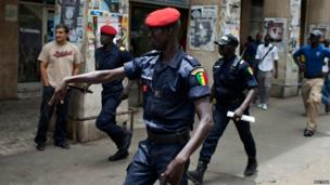 A police officer gestures toward an opposition party protester ahead of the arrival of US President Barack Obama in downtown Dakar on 25 June