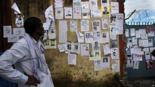 A man looks at a wall which is covered with special announcements and pictures of missing people near the airport gate in Jollygrant, Uttarakhand