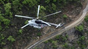 An Indian Air Force helicopter flies over the Gauchar area of Uttarakhand